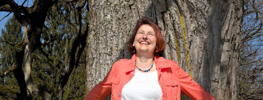 Doris Bürgel lehnt an einem Baum und ist ganz sie selbst