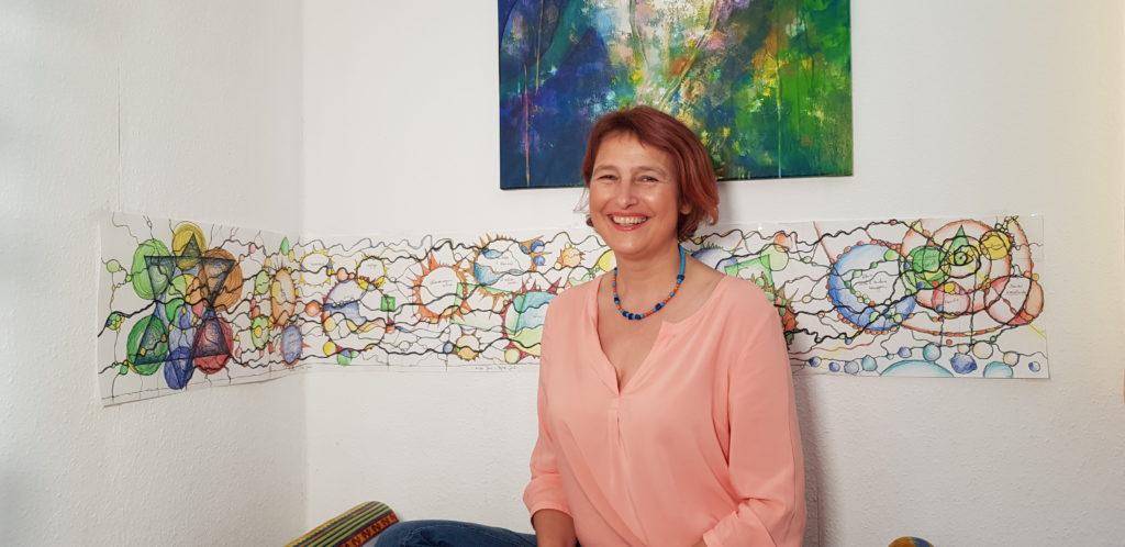 Doris Bürgel sitzt vor einem Bild einer Neurographik und lernt dir ganz du selbst zu sein