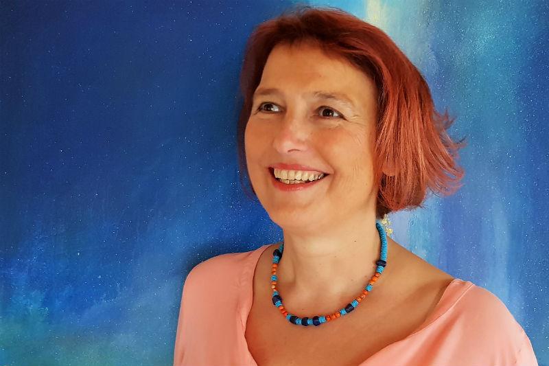Doris Bürgel steht lachend vor einem blauen Bild